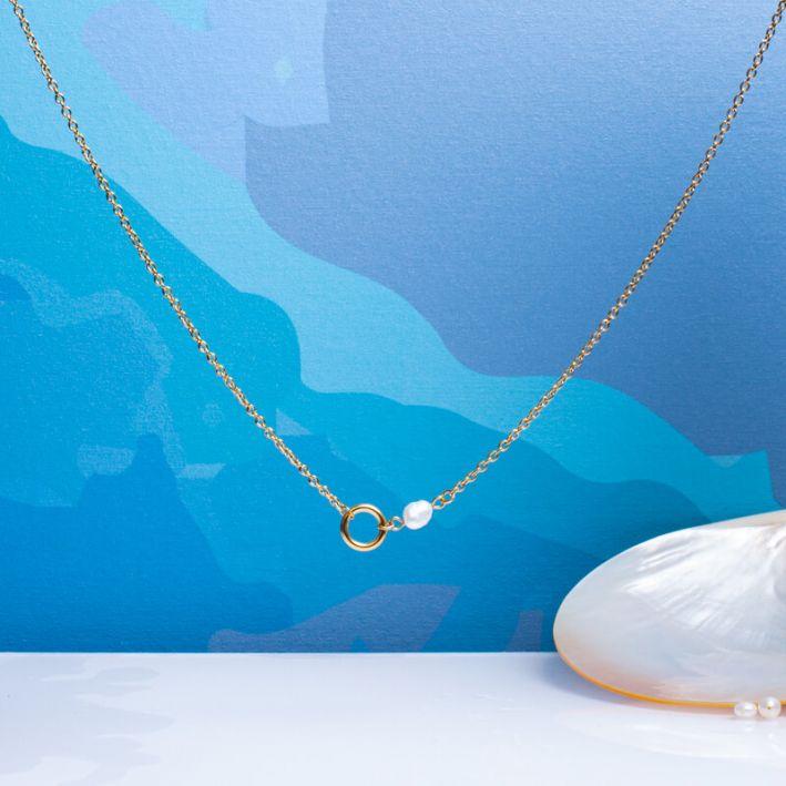 Collier cercle en acier doré et perle de culture blanche sur chaîne dorée