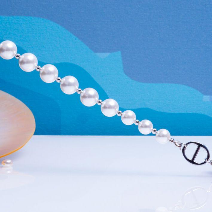 Bracelet perles de nacre blanche sur acier argenté et fermoir bouée