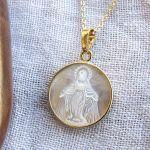 Collier médaille vierge en nacre irisée sur chaîne dorée