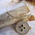 Boucles d'oreilles créoles étoile croix sur une médaille nacr