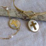 Collier croix dorée en inclusion sur une médaille nacre