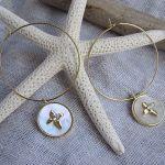 Boucles d'oreilles créoles étoile croix sur une médaille nacre