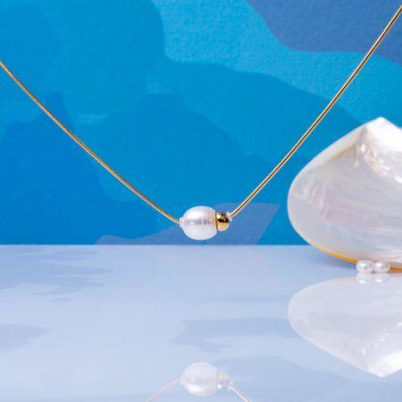 Collier perle de culture blanche et perle en métal doré sur acier doré